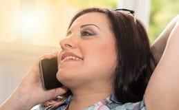 Ευτυχής νέα γυναίκα που μιλά στο τηλέφωνο της Mobil, ελαφριά επίδραση Στοκ Φωτογραφία