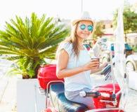 Ευτυχής νέα γυναίκα που πίνει το take-$l*away καφέ κοντά στο κόκκινο μοτοποδήλατό της μέσα Στοκ Φωτογραφίες