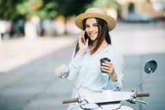 Ευτυχής νέα γυναίκα που πίνει το take-$l*away καφέ κοντά στο μοτοποδήλατό της και που μιλά το τηλέφωνο στην οδό πόλεων στοκ εικόνα με δικαίωμα ελεύθερης χρήσης