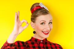 Ευτυχής νέα γυναίκα που παρουσιάζει εντάξει σημάδι με τα δάχτυλα σε ένα κίτρινο backg Στοκ Εικόνες
