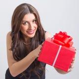 Ευτυχής νέα γυναίκα που παρουσιάζει μεγάλο κόκκινο κιβώτιο δώρων στοκ φωτογραφίες