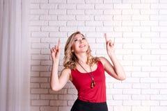 Ευτυχής νέα γυναίκα που παρουσιάζει copyspace υπόδειξη Ξανθό νέο θηλυκό που δείχνει τα δάχτυλα μακριά Διάστημα αντιγράφων για το  στοκ φωτογραφία με δικαίωμα ελεύθερης χρήσης