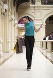Ευτυχής νέα γυναίκα που περπατά στο κατάστημα στοκ φωτογραφία