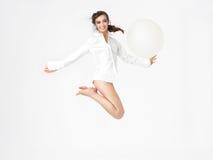 Ευτυχής νέα γυναίκα που πηδά με το μπαλόνι στοκ εικόνες