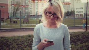 Ευτυχής νέα γυναίκα που στέκεται στην περιοχή πάρκων μεταξύ των buldings που χρησιμοποιεί smartphone της απόθεμα βίντεο