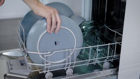 Ευτυχής νέα γυναίκα που τακτοποιεί τα πιάτα στο πλυντήριο πιάτων στο σπίτι απόθεμα βίντεο