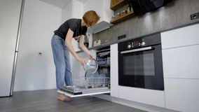 Ευτυχής νέα γυναίκα που τακτοποιεί τα πιάτα στο πλυντήριο πιάτων στο σπίτι φιλμ μικρού μήκους