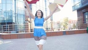 Ευτυχής νέα γυναίκα που τρέχει με τις τσάντες αγορών στα χέρια απόθεμα βίντεο