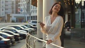 Ευτυχής νέα γυναίκα που φορά το άσπρο πουκάμισο που χρησιμοποιεί το κινητό τηλέφωνο και το χαμόγελο στην οδό κοντά στο δρόμο με τ φιλμ μικρού μήκους