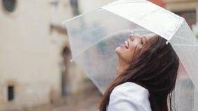 Ευτυχής νέα γυναίκα που χορεύει και που έχει τη διασκέδαση με την ομπρέλα στην οδό της παλαιάς πόλης Όμορφο firl που κοιτάζει και απόθεμα βίντεο