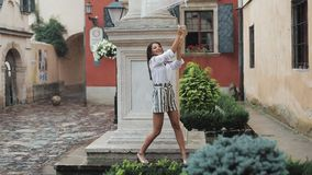 Ευτυχής νέα γυναίκα που χορεύει και που έχει τη διασκέδαση με την ομπρέλα στην οδό της παλαιάς πόλης Όμορφο firl που κοιτάζει και φιλμ μικρού μήκους