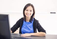 Ευτυχής νέα γυναίκα που χρησιμοποιεί τον υπολογιστή στοκ εικόνα