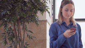 Ευτυχής νέα γυναίκα που χρησιμοποιεί το έξυπνο τηλέφωνο στη λεωφόρο αγορών απόθεμα βίντεο