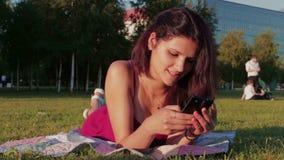 Ευτυχής νέα γυναίκα που χρησιμοποιεί Smartphone στο πάρκο απόθεμα βίντεο