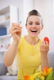 Ευτυχής νέα γυναίκα που χρωματίζει τα αυγά Πάσχας στοκ φωτογραφία