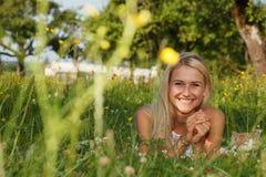Ευτυχής νέα γυναίκα σε ένα λιβάδι θερινών λουλουδιών υπαίθριο Στοκ εικόνες με δικαίωμα ελεύθερης χρήσης