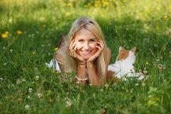 Ευτυχής νέα γυναίκα σε ένα λιβάδι θερινών λουλουδιών υπαίθριο Στοκ Εικόνα