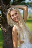 Ευτυχής νέα γυναίκα σε ένα λιβάδι θερινών λουλουδιών υπαίθριο Στοκ Εικόνες