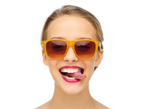 Ευτυχής νέα γυναίκα στα γυαλιά ηλίου που παρουσιάζουν γλώσσα Στοκ Εικόνες