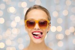 Ευτυχής νέα γυναίκα στα γυαλιά ηλίου που παρουσιάζουν γλώσσα Στοκ Φωτογραφίες