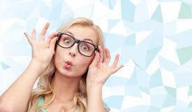 Ευτυχής νέα γυναίκα στα γυαλιά που κάνει το πρόσωπο ψαριών Στοκ Φωτογραφίες