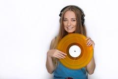 Ευτυχής νέα γυναίκα στα μεγάλα μαύρα επαγγελματικά ακουστικά του DJ που κρατά την καθιερώνουσα τη μόδα κίτρινη ζωηρόχρωμη βινυλίο Στοκ Φωτογραφία