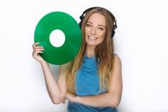 Ευτυχής νέα γυναίκα στα μεγάλα μαύρα επαγγελματικά ακουστικά του DJ που κρατά την καθιερώνουσα τη μόδα πράσινη ζωηρόχρωμη βινυλίο Στοκ Φωτογραφία