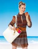 Ευτυχής νέα γυναίκα στην παραλία που τρώει ένα μήλο Στοκ εικόνες με δικαίωμα ελεύθερης χρήσης