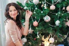 Ευτυχής νέα γυναίκα στη Παραμονή Χριστουγέννων κοντά εορταστικό fir-tree στοκ φωτογραφίες με δικαίωμα ελεύθερης χρήσης