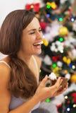 Ευτυχής νέα γυναίκα στις πυτζάμες που έχουν το πρόχειρο φαγητό κοντά στο χριστουγεννιάτικο δέντρο Στοκ Εικόνες