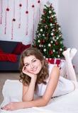 Ευτυχής νέα γυναίκα στο άσπρο φόρεμα που βρίσκεται κοντά στα διακοσμημένα Χριστούγεννα Στοκ Φωτογραφίες