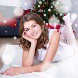 Ευτυχής νέα γυναίκα στο άσπρο φόρεμα που βρίσκεται κοντά στα διακοσμημένα Χριστούγεννα Στοκ φωτογραφίες με δικαίωμα ελεύθερης χρήσης