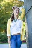 Ευτυχής νέα γυναίκα στο κίτρινο παλτό στην οδό φθινοπώρου Στοκ φωτογραφία με δικαίωμα ελεύθερης χρήσης