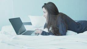 Ευτυχής νέα γυναίκα στο κρεβάτι πίσω από το lap-top Ένα όμορφο κορίτσι στις μπλε πυτζάμες βρίσκεται σε ένα άσπρο κρεβάτι Εργασία  απόθεμα βίντεο
