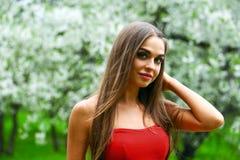 Ευτυχής νέα γυναίκα στο κόκκινο φόρεμα ενάντια στο flo άνοιξη υποβάθρου Στοκ Φωτογραφίες
