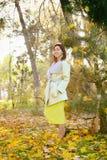 Ευτυχής νέα γυναίκα στο πάρκο την ηλιόλουστη ημέρα φθινοπώρου Εύθυμο όμορφο κορίτσι στο πράσινο πουλόβερ υπαίθρια μεταξύ των κίτρ στοκ εικόνες
