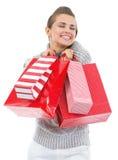 Ευτυχής νέα γυναίκα στο πουλόβερ με τις τσάντες αγορών Χριστουγέννων Στοκ Φωτογραφίες