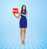Ευτυχής νέα γυναίκα στο φόρεμα με το κόκκινο σημάδι πώλησης Στοκ φωτογραφία με δικαίωμα ελεύθερης χρήσης