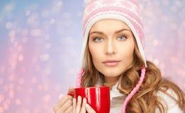 Ευτυχής νέα γυναίκα στο χειμερινό καπέλο με το φλυτζάνι του τσαγιού Στοκ Εικόνες