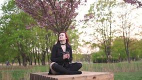 Ευτυχής νέα γυναίκα χορευτών ταξιδιού που απολαμβάνει το ελεύθερο χρόνο σε ένα πάρκο ανθών κερασιών sakura - καυκάσιο λευκό redhe απόθεμα βίντεο