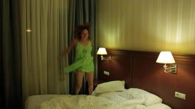 Ευτυχής νέα ενήλικη γυναίκα στο πράσινο φόρεμα που πηδά στο κρεβάτι και που πέφτει έξω του κρεβατιού Χαρά, θετικές συγκινήσεις, α φιλμ μικρού μήκους