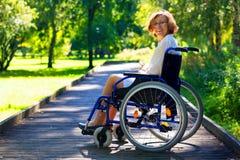 Ευτυχής νέα ενήλικη γυναίκα στην αναπηρική καρέκλα στο πάρκο Στοκ Εικόνες