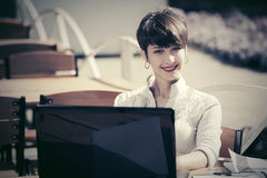 Ευτυχής νέα επιχειρηματίας με το lap-top στον καφέ πεζοδρομίων στοκ φωτογραφίες με δικαίωμα ελεύθερης χρήσης