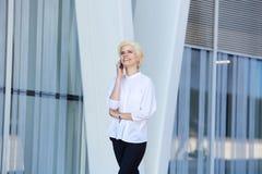 Ευτυχής νέα επιχειρησιακή γυναίκα που περπατά και που μιλά στο τηλέφωνο κυττάρων Στοκ εικόνα με δικαίωμα ελεύθερης χρήσης