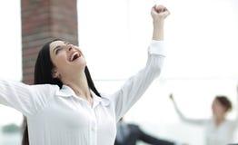 Ευτυχής νέα επιχειρησιακή γυναίκα σε ένα θολωμένο υπόβαθρο γραφείων Στοκ φωτογραφία με δικαίωμα ελεύθερης χρήσης