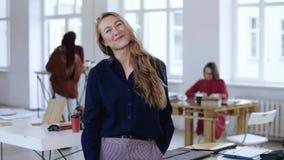 Ευτυχής νέα θετική κύρια επιχειρησιακή γυναίκα με τα μακριά ξανθά μαλλιά στα επίσημα ενδύματα που θέτουν στη κάμερα στο καθιερώνο φιλμ μικρού μήκους
