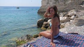 Ευτυχής νέα καλή γυναίκα στη συνεδρίαση μπικινιών στην παραλία, ταλαντεμένος πόδια 4K φιλμ μικρού μήκους