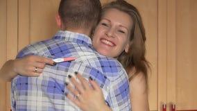 Ευτυχής νέα καυκάσια γυναίκα που αγκαλιάζει τον άνδρα μετά από τη θετική δοκιμή εγκυμοσύνης απόθεμα βίντεο