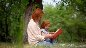 Ευτυχής νέα μητέρα με την ανάγνωση κορών της υπαίθρια απόθεμα βίντεο