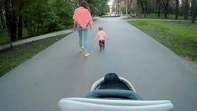 Ευτυχής νέα μητέρα με το τρέξιμο μικρών κοριτσιών στο θερινό πάρκο Η άποψη από τα μάτια ενός πατέρα με ένα καροτσάκι απόθεμα βίντεο